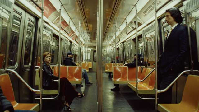In a subway car, Scarlett Johansson sits opposite Adam Driver, who stands, a noticeable distance between the two