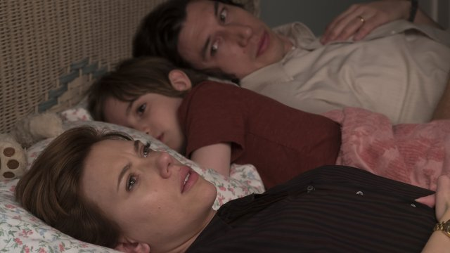 Scarlett Johansson and Adam Driver lie in bed next to each other with their daughter laid in the middle