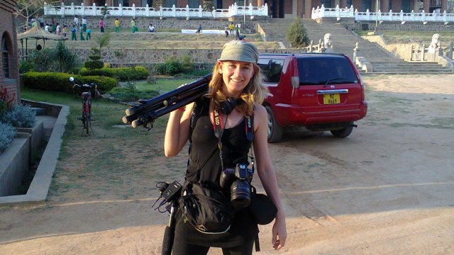 A woman poses holding a camera and tripod