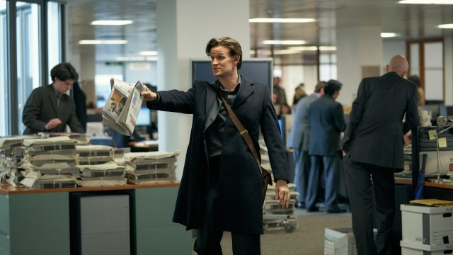 Matt Smith points aminatedly in a busy office, holding a newspaper