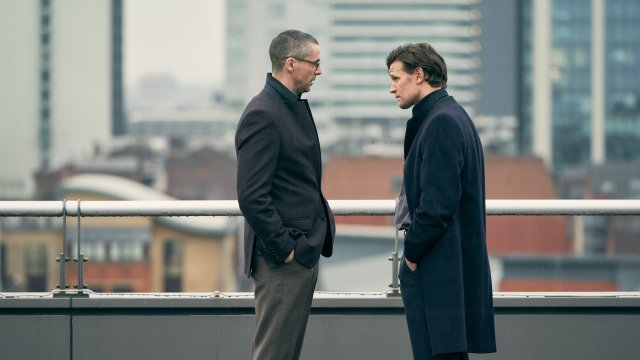 Matt Smith and Matthew Goode talk tensely on a rooftop