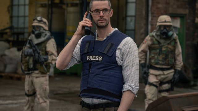 Matthew Goode wearing a press safety vest talks on the phone, with army men around him
