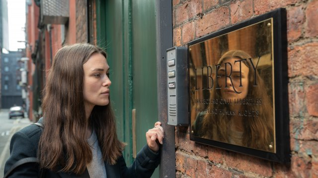 Keira Knightley stands opposite an intercom, looking into her reflection on a gold sign