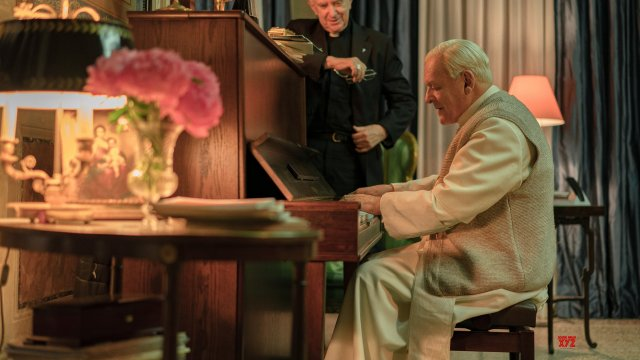 The two popes stand by a piano, one playing and one watching