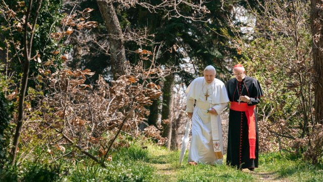 A pope and a cardinal walk through a sunny forest talking.
