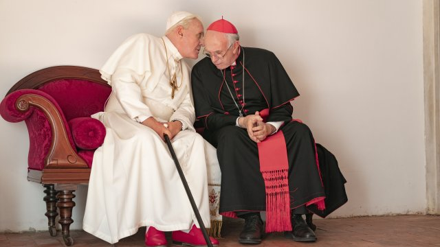 A pope leans in to whisper to cardinal on a bench.