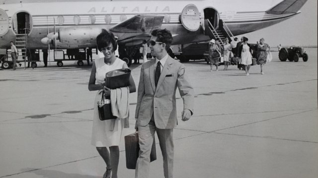 man and woman on a runway, with plane behind them