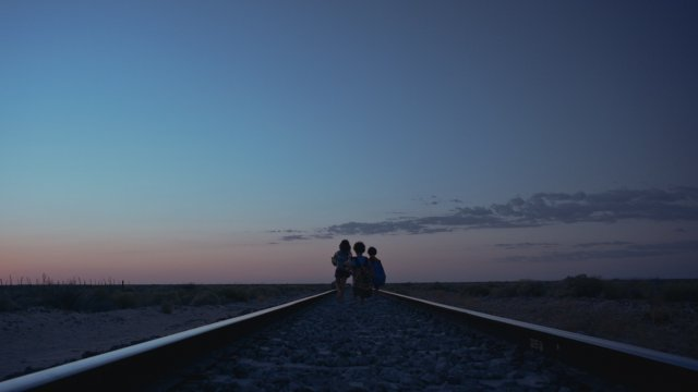 Three small children walk down a railways track into the sunset