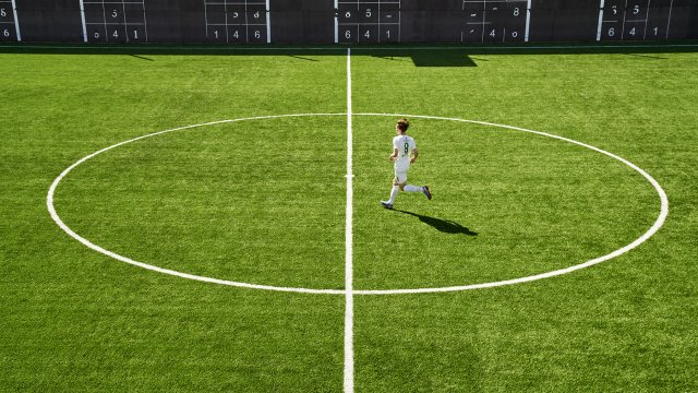 Kid running across artificial football pitch