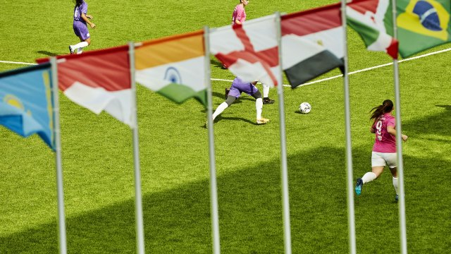 Girls playing football with flags of the world in the foreground