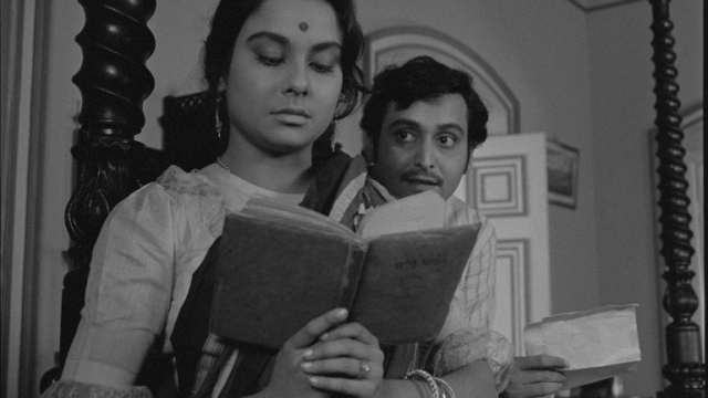 woman reading a book with a man over her shoulder looking at her