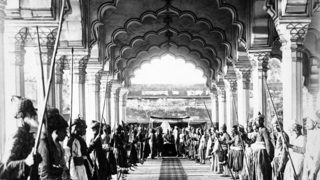 Indian palace archway with a great vanishing point and people on both sides of the hallway