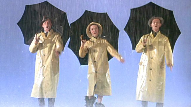 Gene Kelly, Debbie Reynolds and Donald O'Connor sing in the rain, wearing yellow coats and carrying umbrellas