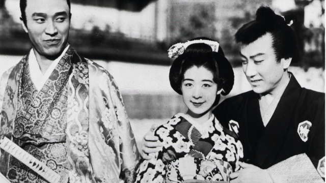 Two men and a woman stand together in traditional Japanese dress.