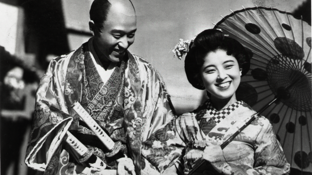 A happy man and a woman stand together in traditional Japanese dress. The woman holds a parasol.