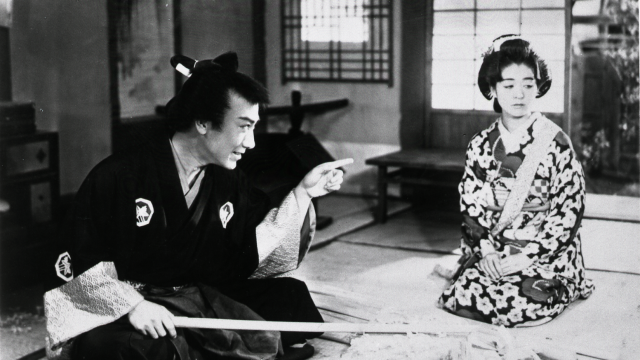 A man and a woman in traditional Japanese dress sit on the floor in a house. The man is reprimanding the woman.