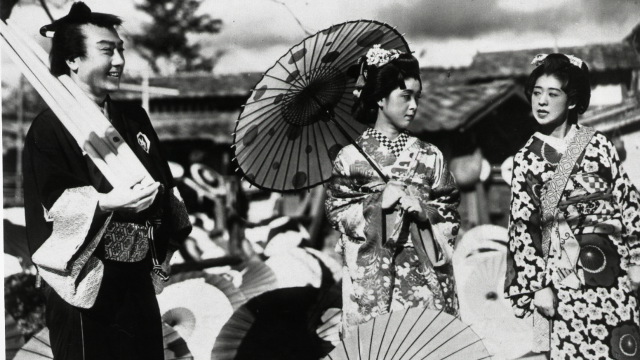 A man and two women in traditional Japanese dress pose together.