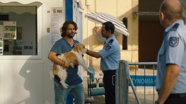 frowning man holding dog at a police checkpoint