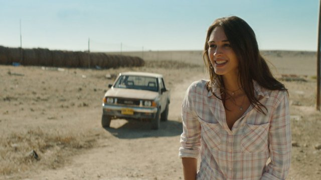 smiling woman in a desert with an old car in the background