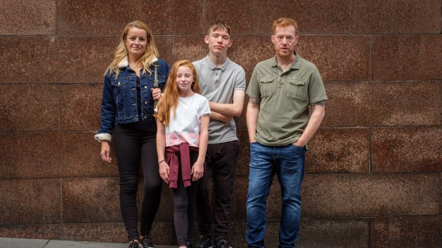 A group of four pose in front of a brick wall - a man, a teenage boy, a teenage girl and a young girl