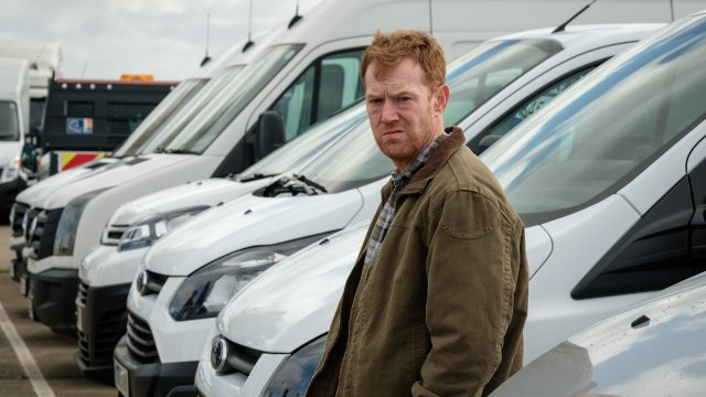 A concerned looking man stands by a row of white vans