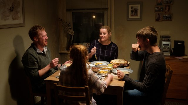 A family sit at a table happily eating dinner