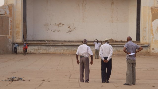 Three men stand facing an empty wall