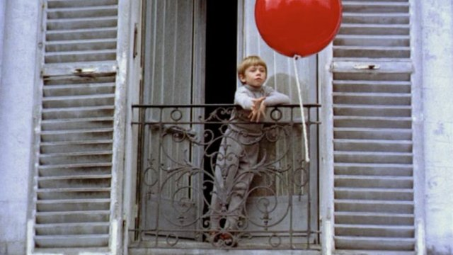 A boy is trying to reach a red balloon from his window
