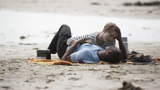 A man and a woman lie on a beach together