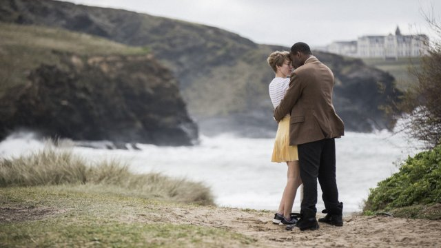 a man and woman hold each other on the coast