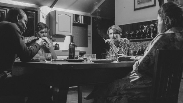 A black and white image of 4 adults sat around a dining table talking