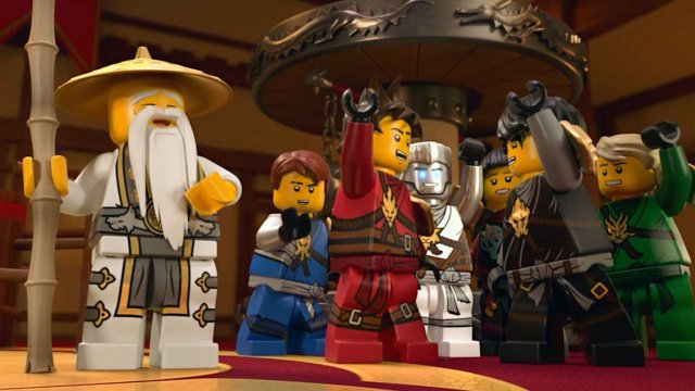 all characters from Lego Ninjago Movie lifting a heavy plate, while a magician is laughing at them