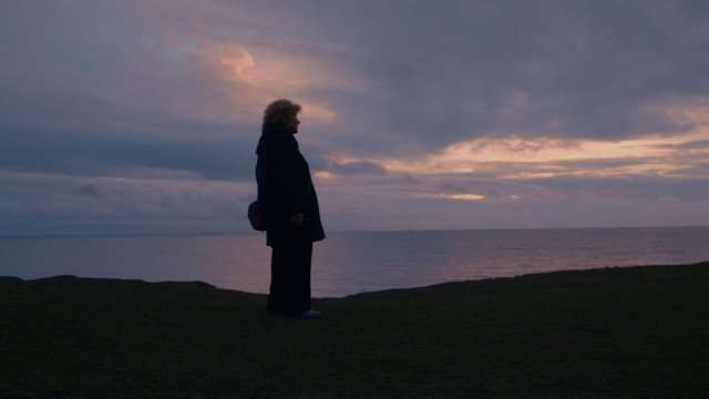 Shirley Collins standing outside with the sun setting