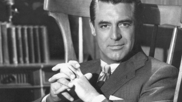 Cary Grant sitting in a chair and smiling at camera