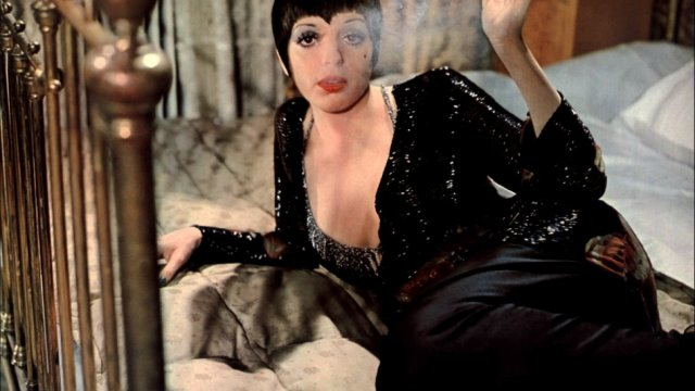 Liza Minelli smoking while lounging on a bed