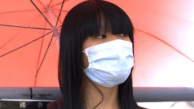 a girl wearing a white face mask is holding a red umbrella