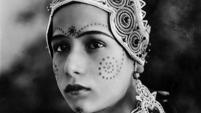 Young, beautiful woman looks into the distance in elaborate Indian jewellery.