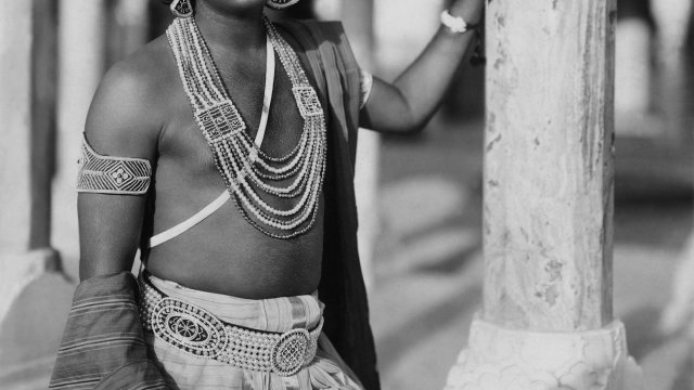 Young Indian man in flamboyant traditional dress standing outside on a verandah.