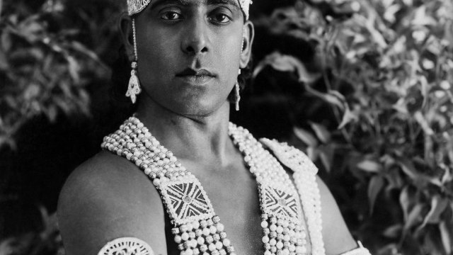 Indian man pose for portrait in elaborate Indian dress.