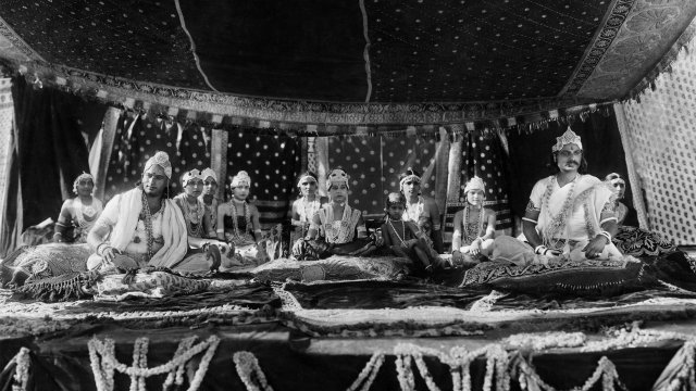 A group of Indian men in traditional clothes sit on a raised stage.