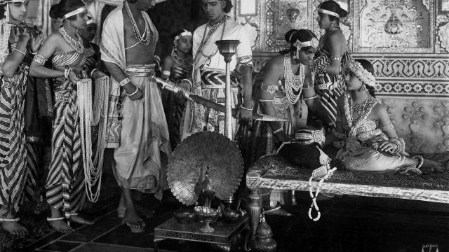 Group of Indian people in a highly decorated, large room look at a man holding a curved sword.
