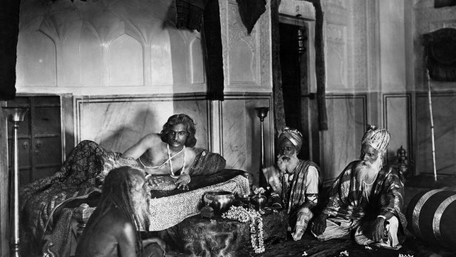 A group of old Indian men lounge in an elaborate hall.