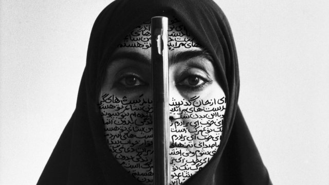 woman with writing on her face wearing black head scarf