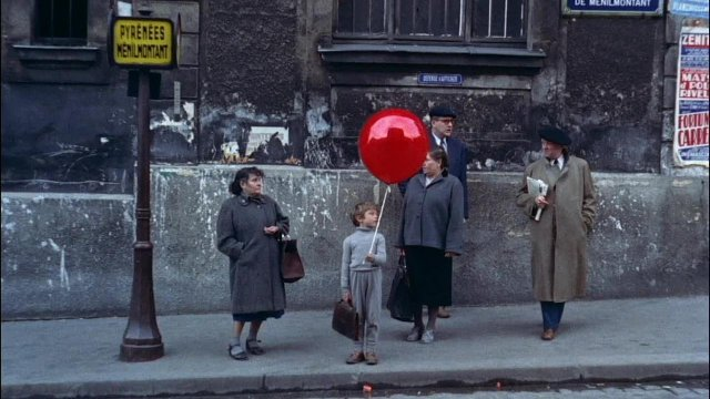 A boy, holding a red ballon is standing on the street between two women
