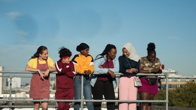 A group of teenagers lean on a rail on a rooftop terrace.