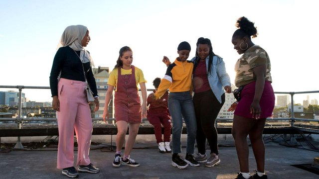 A diverse group of teenagers are having fun on a rooftop terrace.
