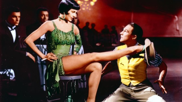 Gene Kelly kneels before a sultry dancer in a green dress.