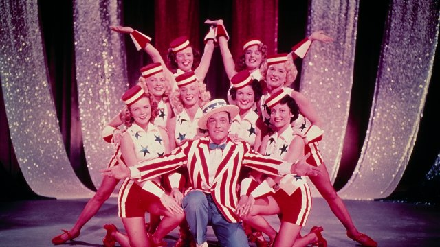 Gene Kelly fronts a group of show dancers in bright costumes.
