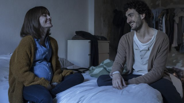 Man and a woman sit on a bed laughing together