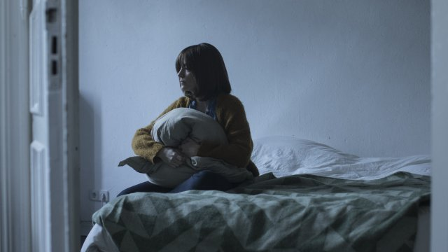 Woman sat on bed holding pillow looking sad